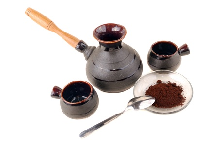 Clay coffee maker with cups and wooden handles on a white background photo