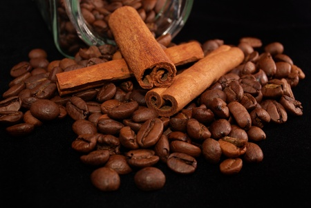 stick of cinnamon: Brown fried grains of coffee and stick cinnamon scattered on a black background  Stock Photo