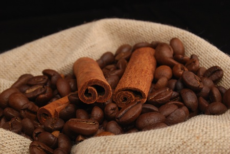 Brown fried grains of coffee and stick cinnamon scattered on a black background  photo
