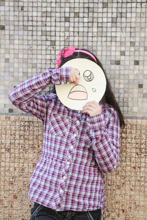 sad girl with a mask drying the tears photo