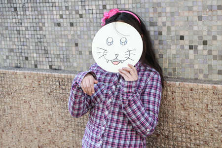 Girl with cat mask waving her hand like a paw photo