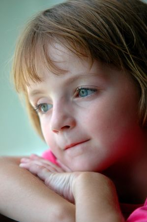 Portrait of Little Girl looking out window photo