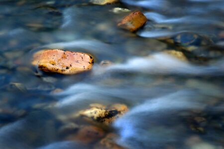 Rock in Stream River with Fast Moving Water Flowing Past