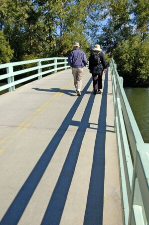 bridge over water: couple walking across bridge over water