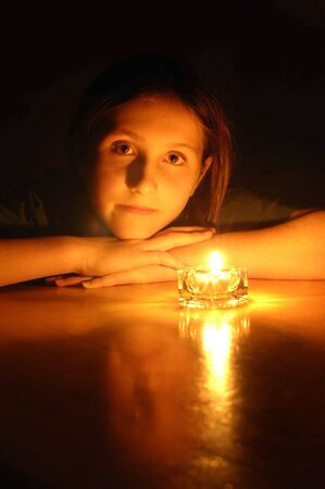 glancing: young girl portrait by glow of candlelight