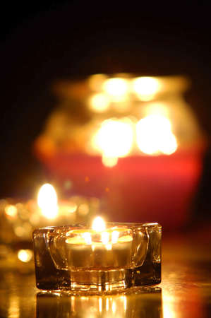 glancing: closeup of several candles glowing with a dark background