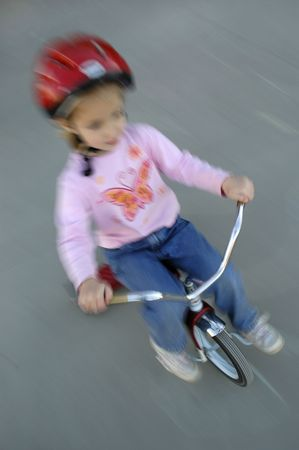 casco rojo: moci�n disparo de ni�a en bicicleta con casco rojo
