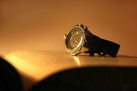 sepia toned watch on an open book