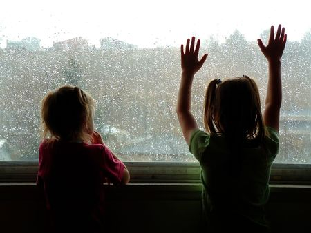 two little kids looking out window on rainy day