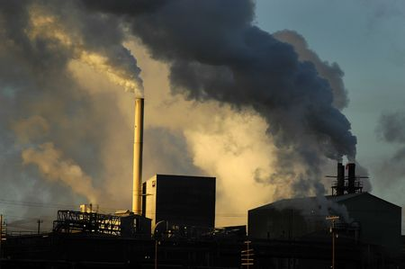 soil pollution: smokestacks from a factory spewing smoke and pollution into the air Stock Photo