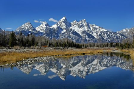 Teton mountain range reflecting in river water with surrounding plants and trees photo
