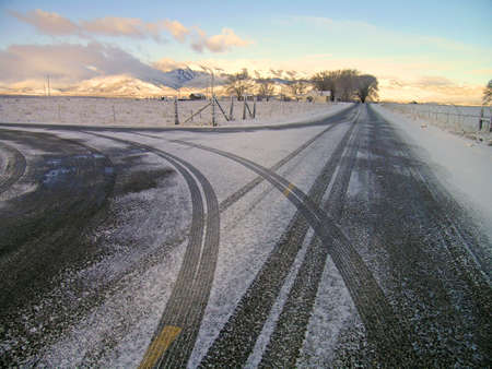 blanketed: Winter country road with crossroad and car tracks in snow Stock Photo