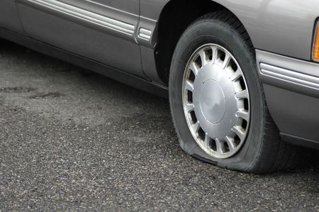 spare car: Car on the road with a flat tire not moving