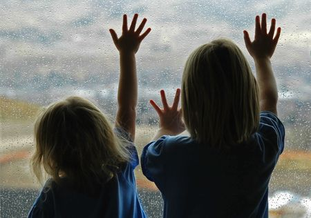 sadly: Little girls standing by window with raindrops on it on a rainy day Stock Photo