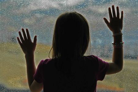 Little girl standing by window with raindrops on it on a rainy day