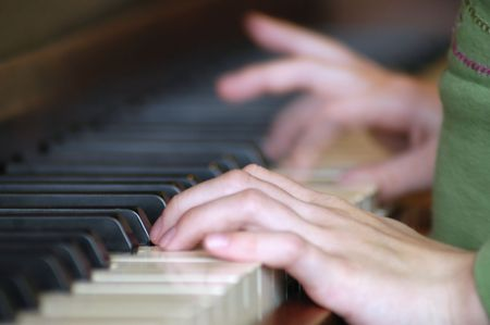 Close up of the hands of a child learning to play the piano photo