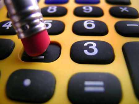 Closeup of a pencil pushing buttons on a calculator Stock Photo