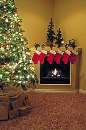 camino natale: Fronte camera decorata per Natale con albero di Natale e calze camino Archivio Fotografico