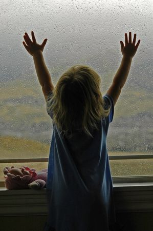 Little girl standing by window with raindrops on it on a rainy day photo