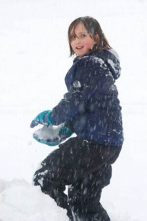 One little girl playing in the snow thworing a snowball