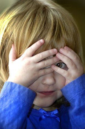 Little girl playing peek a boo with her hands Stock Photo - 736835