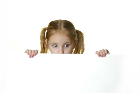 Little girl looking over the edge of a white sign she is holding