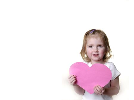 ponytails: Little girl dressed in white holding a valentine heart Stock Photo