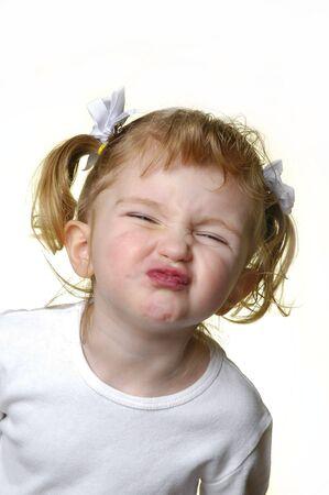 making faces: Bambina vestita di bianco che si affaccia espressioni Archivio Fotografico