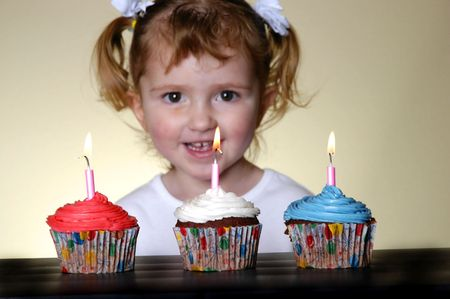 Three cupcakes side by side with little girl looking at them photo