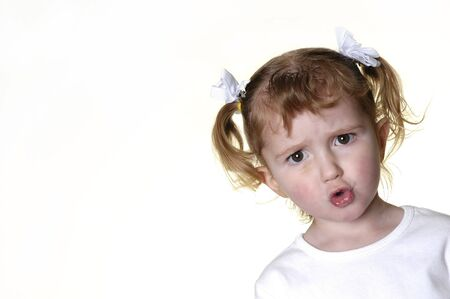 Little girl dressed in white making faces expressions photo
