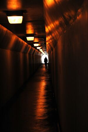 emerge: Long tunnel walkway with person at the end