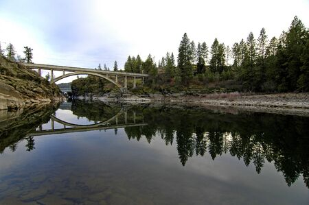 Reflection of bridge and forrest in river water photo