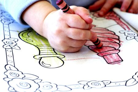 Little child colring in coloring book with crayons photo