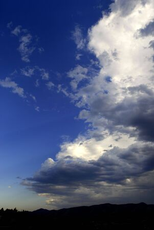 View of white and gray storm clouds in blue sky photo