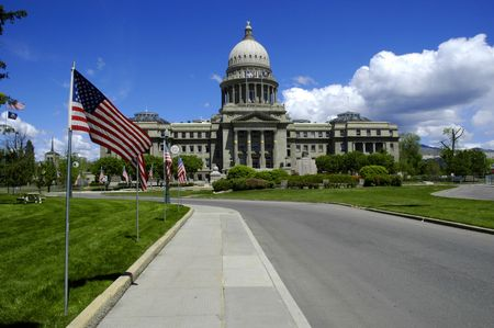State capital building with flags and sky