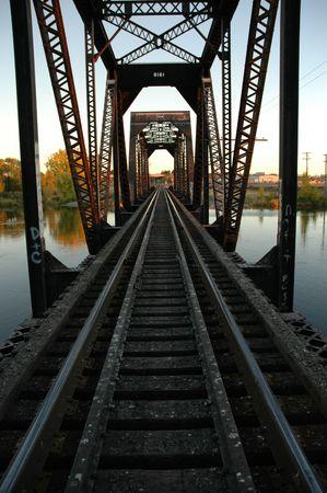 bridged: Railroad tracks on scaled bridge crossing river into the distance