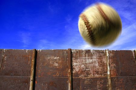 homerun: Baseball flying through the air with clouds sky and fence in background
