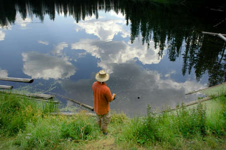 Fishing in lake with reflection of trees and sky photo