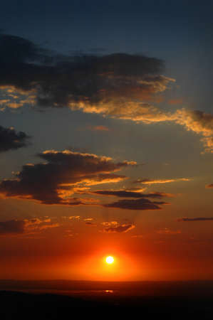 Sunset with sun and clouds in orange and golden light photo