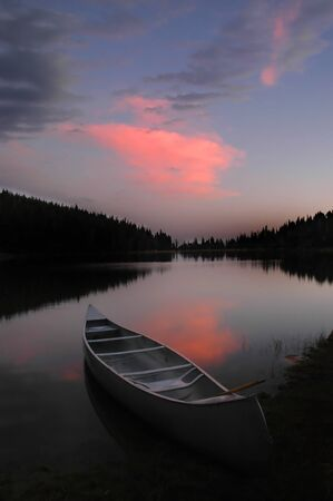 Evening sunset in soft pink and blue light and canoe in lake photo