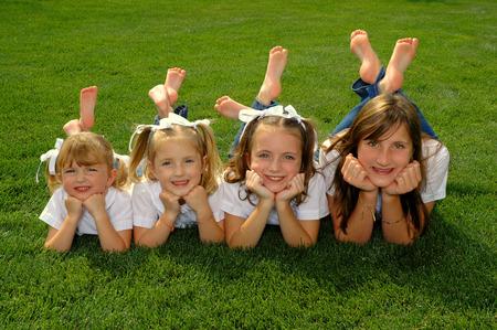 Vier zussen op een rij, gekleed in witte shirts
