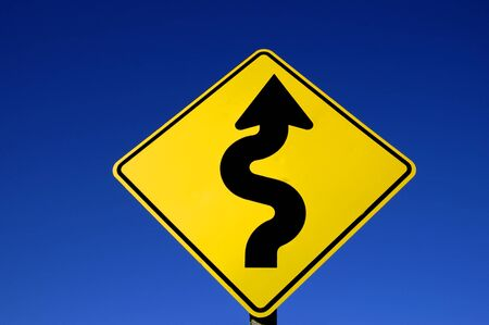 slowdown: Yellow street sign with curves against blue sky
