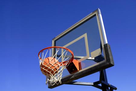swish: Action shot of basketball going through basketball hoop and net