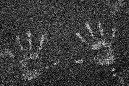 crack: Detailed closeup of white handprints on textured dark wall Stock Photo
