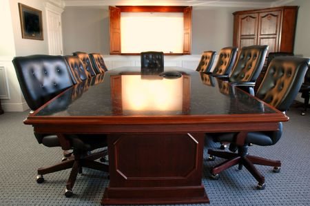 Conference room table with several leather chairs