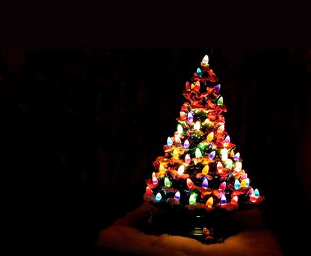 Christmas tree decorated with glowing colored lights and black background photo