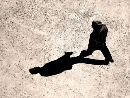 shadow: Man walking on sidewalk with black shadow