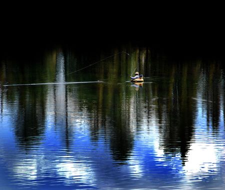foiliage: Fishing in lake with reflection of trees and sky Stock Photo