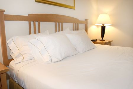 white sheet: Group of several white pillows on a bed with headboard