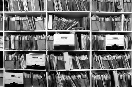 oficina desordenada: Estantes de la oficina por completo de archivos y de cajas